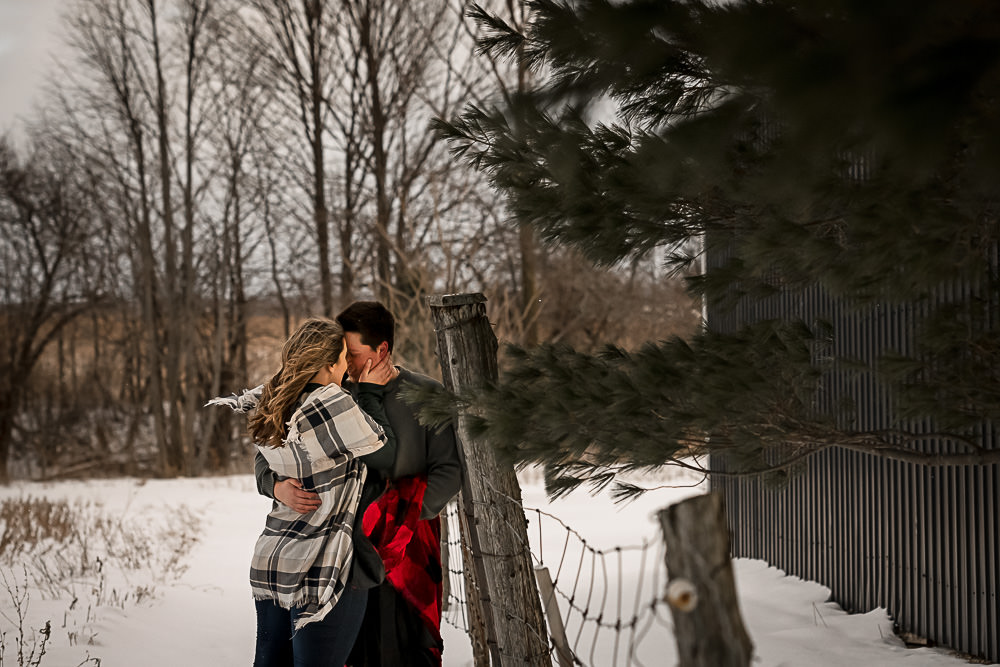 couple snuggling again wood fence at winter engagement session in Owen Sound