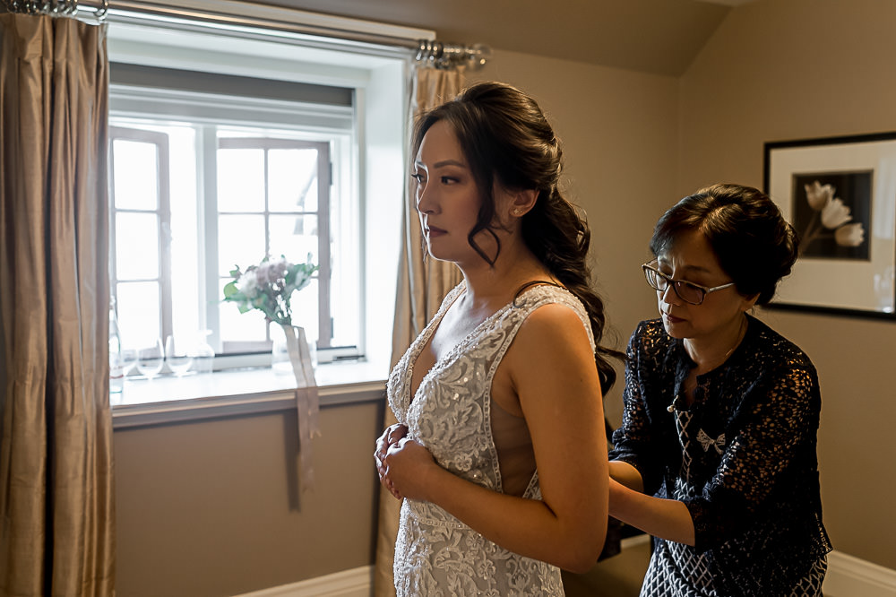 Mother helping bride in suite at Ancaster Mill