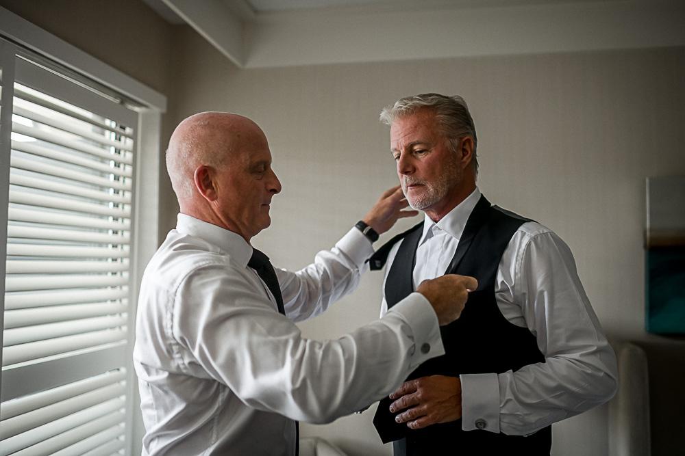 best man helping groom dress