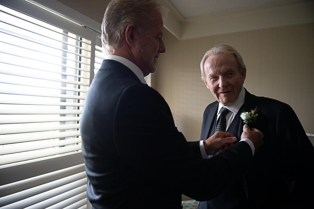 dad helping groom get dressed