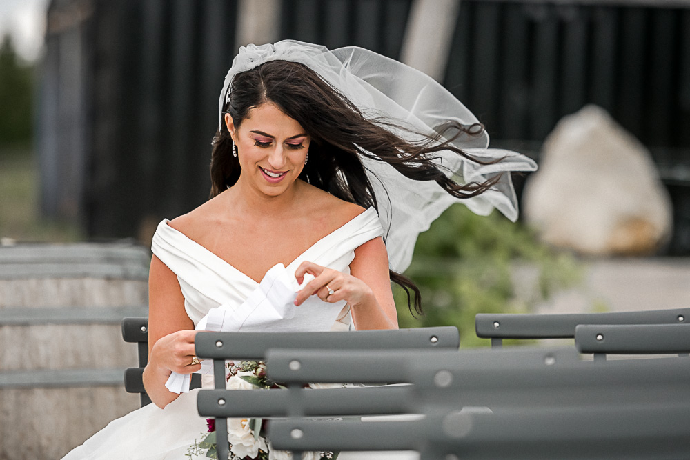 bride reading letter from groom in wind