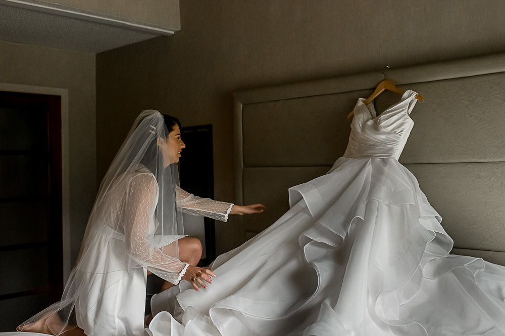 bride reaching for dress