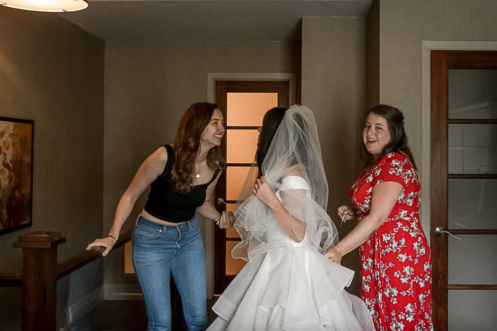 bride getting dressed with friends