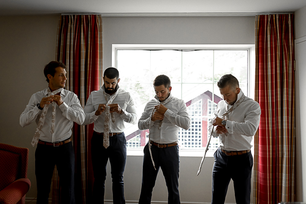 groomsmen putting on ties together