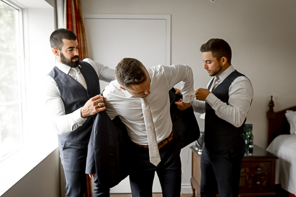 groomsmen getting groom dressed