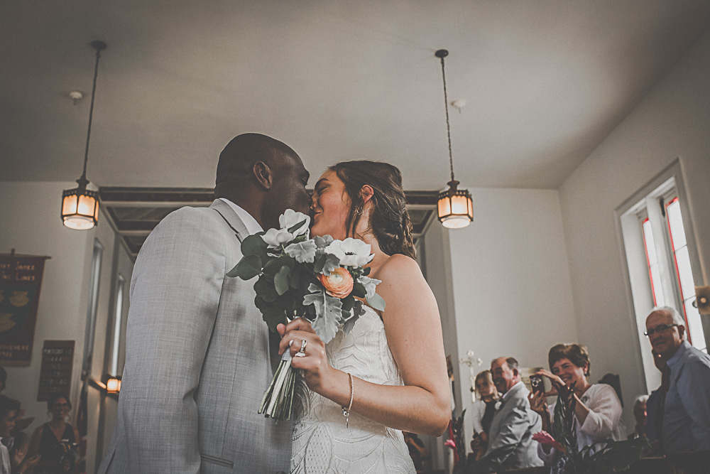 bride and groom kissing in chapel