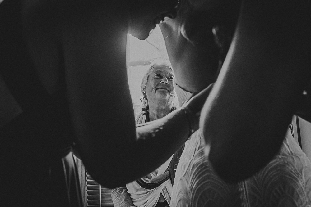 mother looking at bride getting ready