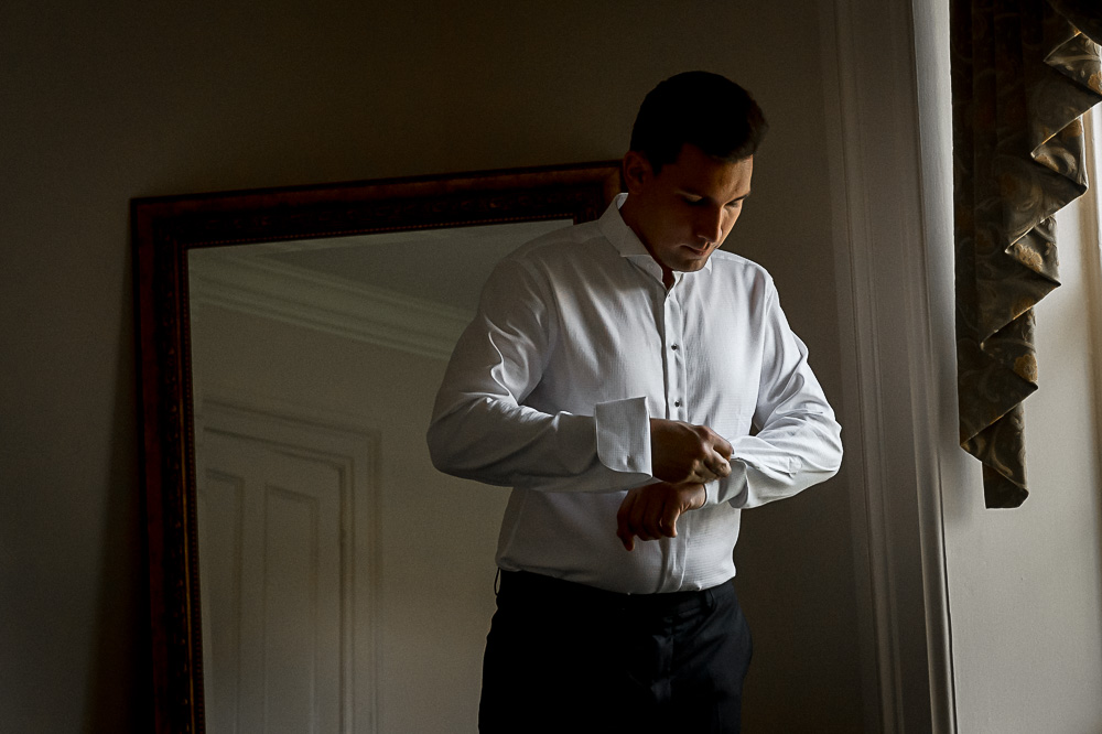 groom getting dressed in front of window