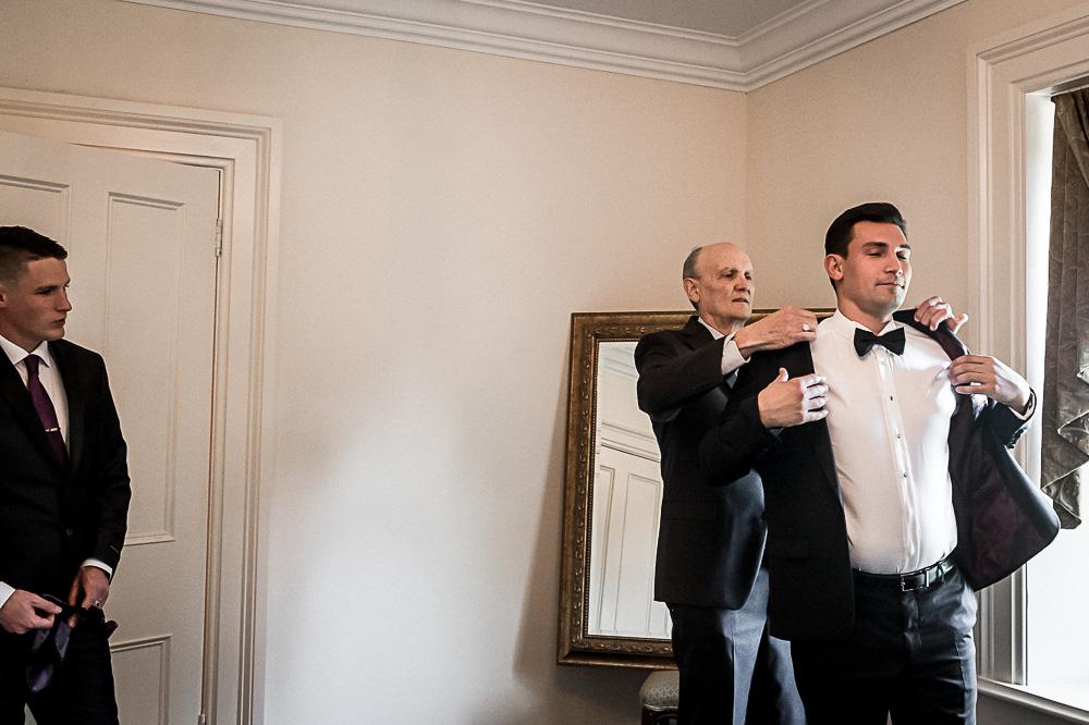 dad helps groom in jacket