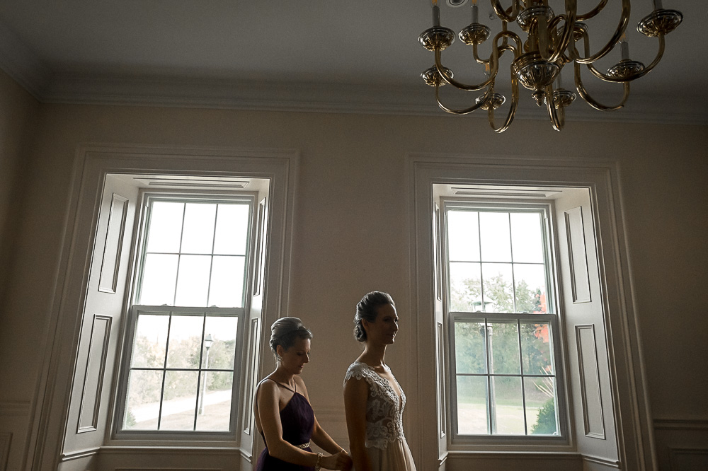 sister helps bride in gown